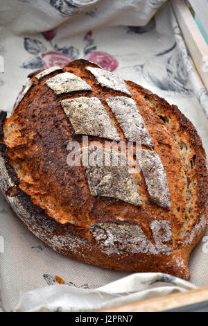 A loaf of artisanal bread in a rustic traditional bakery. - Stock Photo
