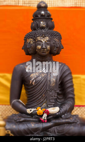 Close-up of meditate Buddha statue with multi faces in soft-focus in the orange background - Thailand - Bangkok - Stock Photo