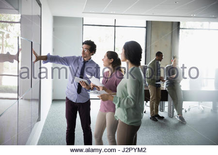 Business people talking at projection screen in conference room meeting - Stock Photo