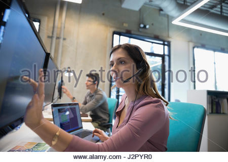 Technical support operator with headset working at laptop and computer - Stock Photo