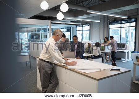 Male architects with laptop drafting and reviewing blueprints in office - Stock Photo
