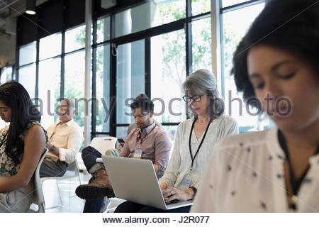 Business people taking notes, working at laptop in conference audience - Stock Photo