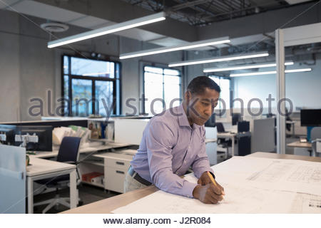 Male African American architect drafting and reviewing blueprints in office - Stock Photo