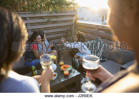 Family hanging out, drinking wine and using digital tablet on sunny deck - Stock Photo