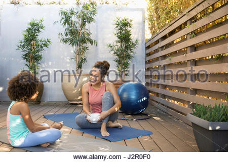 African American mother and daughter eating cereal on yoga mats on deck - Stock Photo
