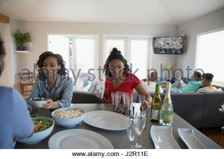 African American teenage sisters eating in kitchen - Stock Photo