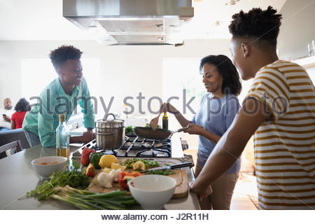 African American mother and teenage sons cooking at stove in kitchen - Stock Photo