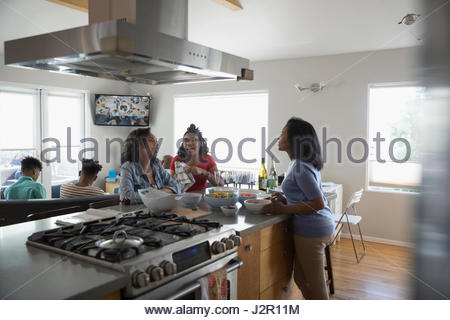 African American mother and teenage daughters cooking and eating in kitchen - Stock Photo