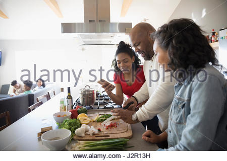 African American father and daughters cooking in kitchen - Stock Photo