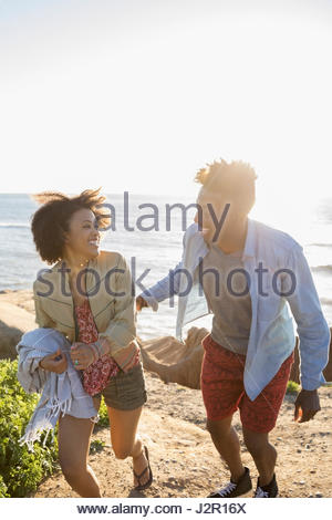 Playful young couple walking on sunny beach - Stock Photo