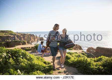 Young couple walking arm in arm with guitar on sunny beach - Stock Photo