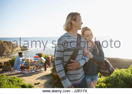 Affectionate young couple walking arm in arm with guitar on sunny beach - Stock Photo