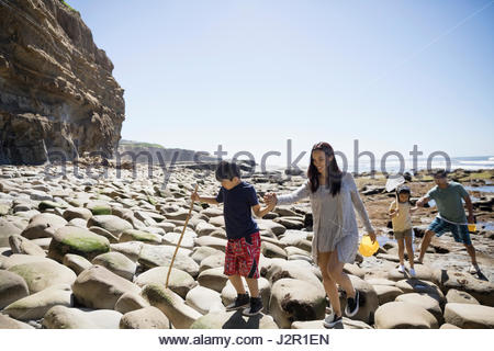 Latino family walking on sunny craggy beach - Stock Photo