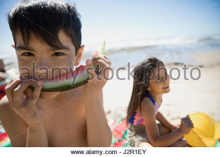 Portrait Latino boy eating watermelon on sunny beach - Stock Photo
