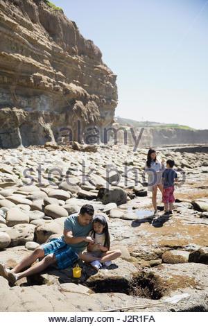 Latino family playing on sunny craggy beach - Stock Photo