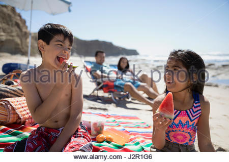 Latino brother and sister eating watermelon on sunny beach - Stock Photo