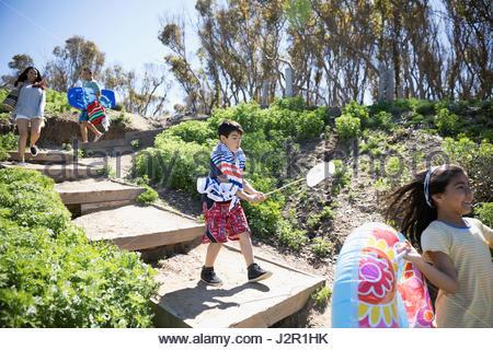 Latino family arriving, running down sunny beach steps - Stock Photo