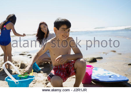 Smiling Latino boy making sandcastle on sunny beach - Stock Photo