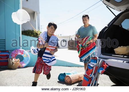 Father and son loading car for beach trip in sunny driveway - Stock Photo