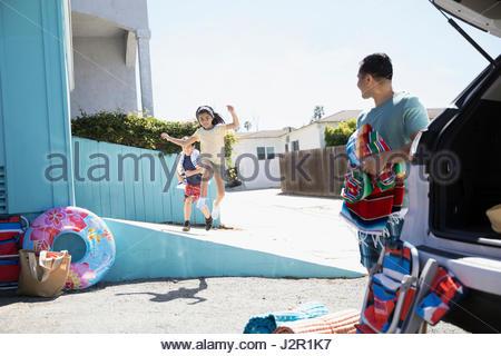 Latino family preparing for beach trip in sunny driveway - Stock Photo