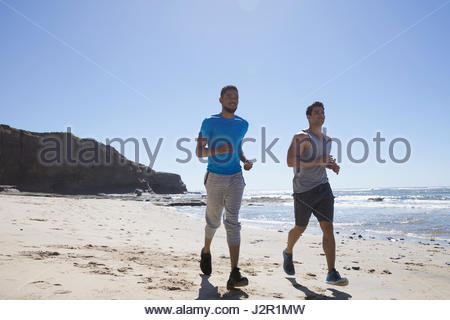 Male joggers running on sunny beach - Stock Photo