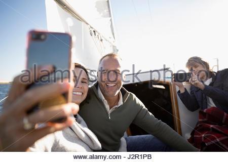 Senior couple with camera phone taking selfie on sailboat - Stock Photo