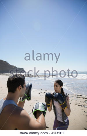 Man and woman boxing on sunny beach - Stock Photo