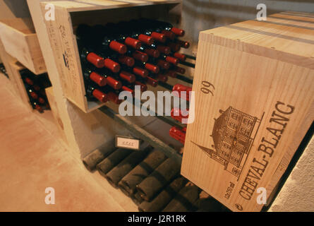Fine luxury very expensive wine bottles of Château Cheval Blanc, some dated 1945, ageing in the Chateau cellars. - Stock Photo