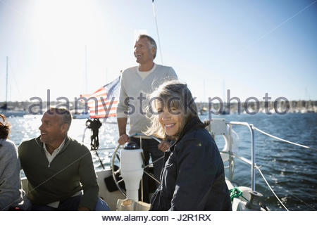 Portrait senior woman on sunny sailboat with friends - Stock Photo