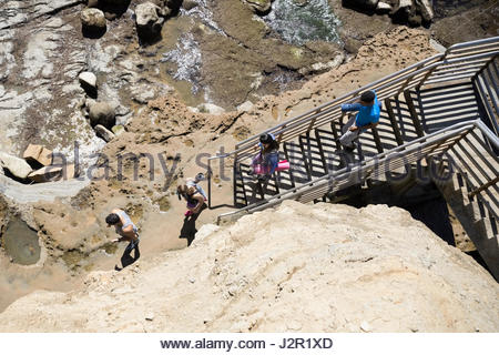 Young men and women with yoga mats descending stairs above craggy beach - Stock Photo