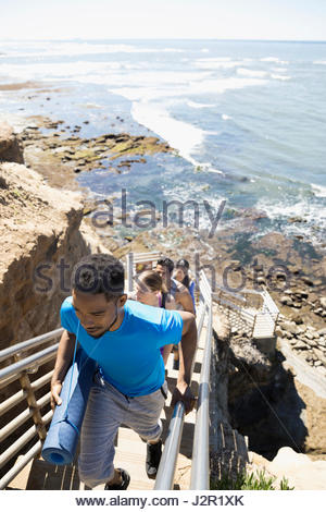 Young men and women with yoga mats climbing stairs above sunny ocean - Stock Photo