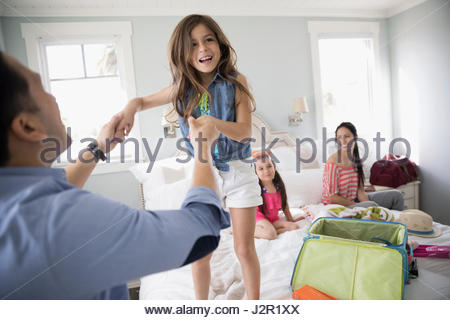 Playful father and daughter jumping on bed, packing for vacation - Stock Photo