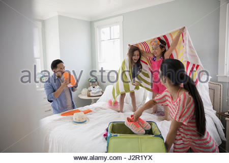 Family packing for vacation, playing on bed - Stock Photo