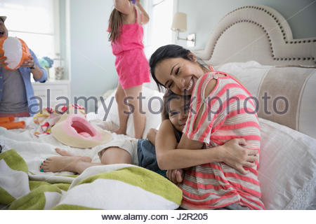 Portrait smiling mother hugging daughter on bed - Stock Photo