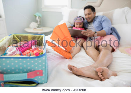 Father and daughter wearing flippers packing for vacation, using digital tablet on bed - Stock Photo