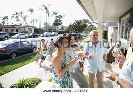 Multi-generation family toasting white wine glasses on summer beach house porch - Stock Photo