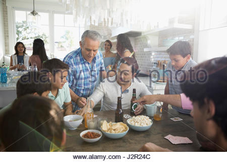 Multi-generation family playing cards, eating and drinking at beach house kitchen table - Stock Photo
