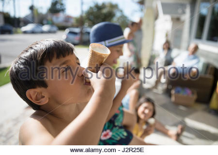 Boy eating melting ice cream cone on summer beach house porch - Stock Photo