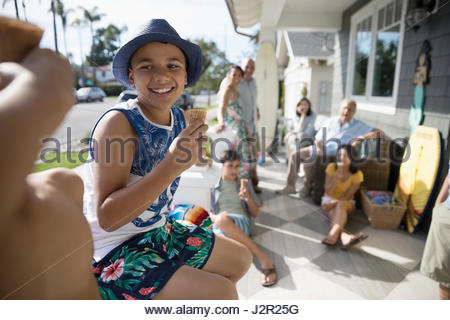 Smiling boy eating ice cream cone with family on summer beach house porch - Stock Photo