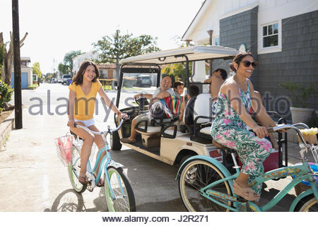 Family with beach cruiser bicycles and golf cart in summer beach house driveway - Stock Photo