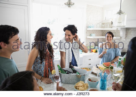 Family and friends drinking and eating in beach house kitchen - Stock Photo