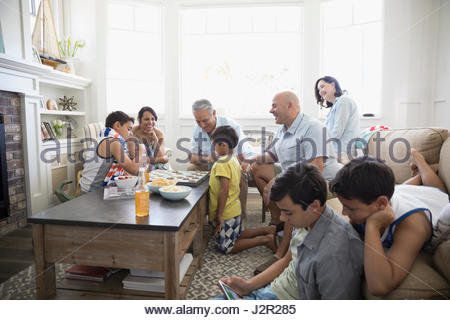 Multi-generation family playing checkers and using digital tablet in beach house living room - Stock Photo