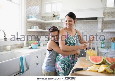 Portrait smiling son hugging mother making lemonade in beach house kitchen - Stock Photo