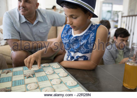 Boy playing checkers with seashells in beach house - Stock Photo