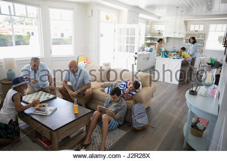Multi-generation family playing checkers and using digital tablet in beach house - Stock Photo