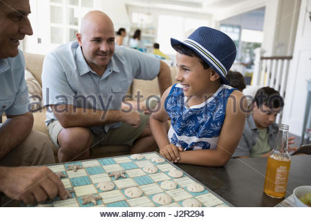 Multi-generation family playing checkers in beach house - Stock Photo
