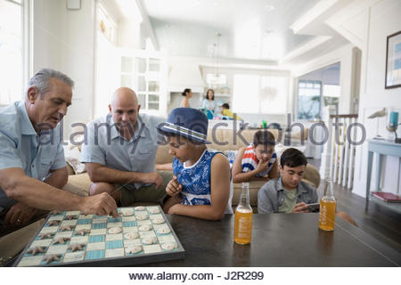 Multi-generation men and boys playing checkers and using digital tablet in beach house - Stock Photo