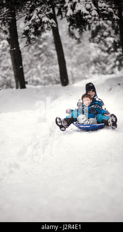 Two brothers having fun in winter with a sledge - Stock Photo