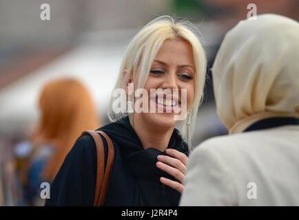 A blonde girl talks to her muslim friend - Stock Photo