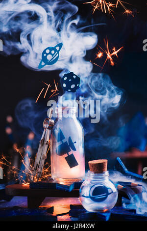 Astronomy themed still life with space station, planets and asteroid inside jars on a dark background - Stock Photo